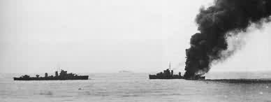 HMS Fearless on fire with HMS Forester standing by.